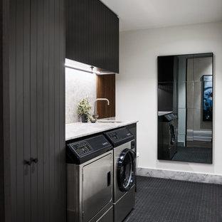 Foto di una sala lavanderia design con lavello sottopiano, ante nere, pareti bianche, lavatrice e asciugatrice affiancate, pavimento nero e top bianco