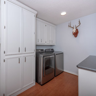 Foto di una lavanderia multiuso moderna di medie dimensioni con ante in stile shaker, ante bianche, top in granito, pareti bianche, pavimento in legno verniciato, lavatrice e asciugatrice affiancate, pavimento marrone e top nero