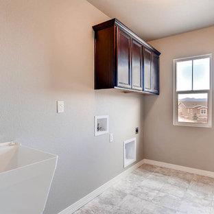 Inspiration för en mellanstor amerikansk parallell tvättstuga enbart för tvätt, med en allbänk, skåp i shakerstil, skåp i mörkt trä, grå väggar, linoleumgolv, en tvättmaskin och torktumlare bredvid varandra och grått golv