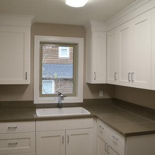 Idee per una grande sala lavanderia tradizionale con lavello da incasso, ante in stile shaker, ante bianche, top piastrellato, pareti grigie, pavimento in travertino e lavatrice e asciugatrice affiancate