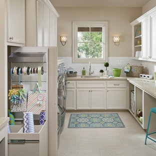 Design ideas for a large traditional u-shaped utility room in Houston with a single-bowl sink, recessed-panel cabinets, white cabinets, limestone worktops, porcelain flooring, a side by side washer and dryer, beige walls and beige worktops.