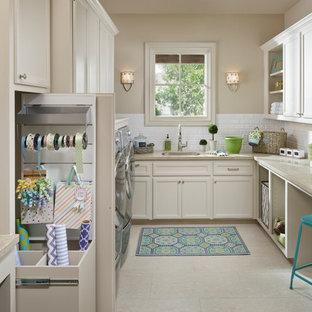 Inredning av ett klassiskt stort beige u-format beige grovkök, med en enkel diskho, luckor med infälld panel, vita skåp, bänkskiva i kalksten, klinkergolv i porslin, en tvättmaskin och torktumlare bredvid varandra och beige väggar