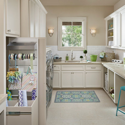 Inspiration for a large timeless u-shaped porcelain tile utility room remodel in Houston with a single-bowl sink, recessed-panel cabinets, white cabinets, limestone countertops, a side-by-side washer/dryer, beige walls and beige countertops