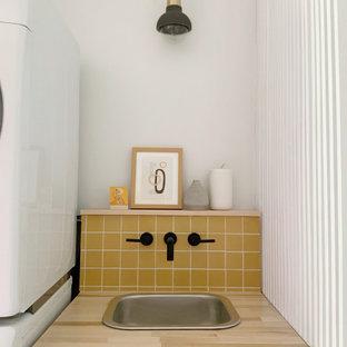 Immagine di una lavanderia bohémian con lavello da incasso, ante bianche e paraspruzzi giallo