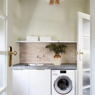 Bild på en grå grått tvättstuga, med en enkel diskho, bänkskiva i täljsten, stänkskydd i terrakottakakel, gröna väggar och klinkergolv i terrakotta