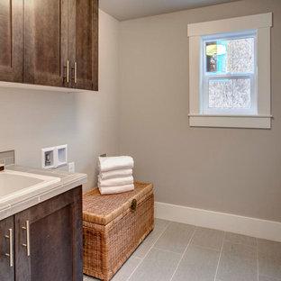 Foto di una sala lavanderia tradizionale di medie dimensioni con lavello da incasso, ante lisce, ante in legno bruno, top piastrellato, pareti grigie, pavimento con piastrelle in ceramica e lavatrice e asciugatrice affiancate