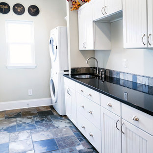 Inspiration for a medium sized contemporary single-wall utility room in Columbus with white cabinets, beige walls, slate flooring, a stacked washer and dryer, black floors, black worktops, recessed-panel cabinets and a submerged sink.