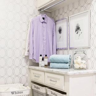 Inredning av en klassisk liten tvättstuga, med vita skåp, träbänkskiva, klinkergolv i porslin, vitt golv, vita väggar, en tvättmaskin och torktumlare bredvid varandra och luckor med infälld panel