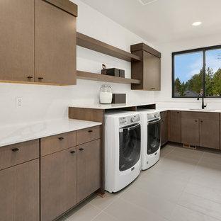 Foto di una grande sala lavanderia minimal con lavello sottopiano, ante lisce, top in quarzo composito, pareti bianche, lavatrice e asciugatrice affiancate, pavimento grigio, top bianco e ante in legno scuro