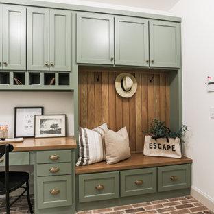 Immagine di una grande sala lavanderia chic con ante in stile shaker, ante verdi, top in legno, pavimento in mattoni, lavatrice e asciugatrice affiancate, pavimento rosso e top marrone