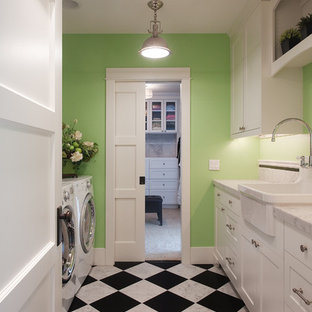 Inredning av en klassisk parallell tvättstuga, med gröna väggar, en rustik diskho, skåp i shakerstil, vita skåp, marmorbänkskiva, marmorgolv, en tvättmaskin och torktumlare bredvid varandra och flerfärgat golv