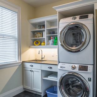 Medium sized nautical single-wall utility room in Toronto with a submerged sink, shaker cabinets, white cabinets, granite worktops, beige walls, slate flooring and a stacked washer and dryer.