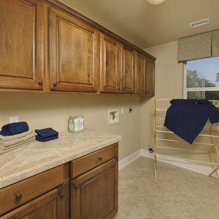 Foto på en liten vintage beige linjär tvättstuga enbart för tvätt, med luckor med upphöjd panel, skåp i mellenmörkt trä, kaklad bänkskiva, beige väggar, klinkergolv i porslin, en tvättmaskin och torktumlare bredvid varandra och beiget golv
