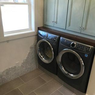 Idéer för en klassisk bruna tvättstuga, med turkosa skåp, träbänkskiva, klinkergolv i keramik och grått golv