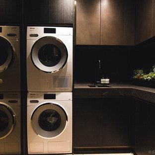 Esempio di una sala lavanderia minimalista di medie dimensioni con lavello sottopiano, ante lisce, ante in legno bruno, top piastrellato, pareti grigie, pavimento in gres porcellanato, lavatrice e asciugatrice a colonna, pavimento beige e top grigio
