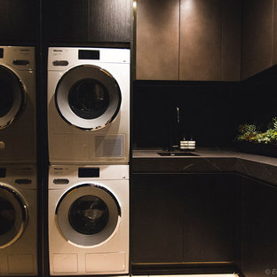 Example of a mid-sized minimalist l-shaped porcelain tile and beige floor dedicated laundry room design in Sydney with an undermount sink, flat-panel cabinets, dark wood cabinets, tile countertops, gray walls, a stacked washer/dryer and gray countertops