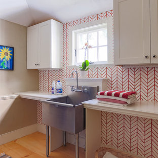 Photo of a small country single-wall dedicated laundry room in Boston with an utility sink, white cabinets, shaker cabinets, multi-coloured walls and medium hardwood floors.