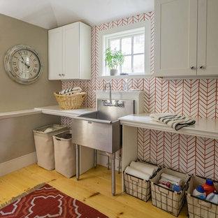 Réalisation d'une buanderie champêtre dédiée avec un évier utilitaire, un placard avec porte à panneau encastré, des portes de placard blanches, un mur rouge et un sol en bois clair.