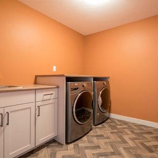 Inredning av en mellanstor linjär tvättstuga enbart för tvätt, med en enkel diskho, skåp i shakerstil, vita skåp, laminatbänkskiva, orange väggar och en tvättmaskin och torktumlare bredvid varandra
