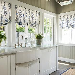 Exempel på ett stort klassiskt grovkök, med en rustik diskho, skåp i shakerstil, vita skåp, marmorbänkskiva, grå väggar och tvättmaskin och torktumlare byggt in i ett skåp