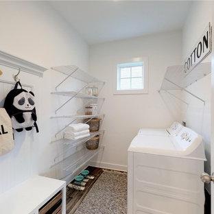 Bild på en mellanstor amerikansk tvättstuga enbart för tvätt, med vita väggar, linoleumgolv, en tvättmaskin och torktumlare bredvid varandra och grått golv