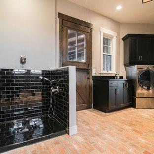 デンバーの大きいラスティックスタイルのおしゃれな家事室 (黒いキャビネット、人工大理石カウンター、グレーの壁、レンガの床、左右配置の洗濯機・乾燥機、赤い床、シェーカースタイル扉のキャビネット) の写真