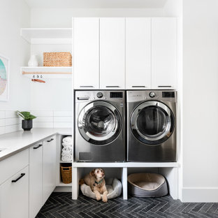 This is an example of a modern l-shaped laundry room in Vancouver with an undermount sink, flat-panel cabinets, quartz benchtops, white splashback, white benchtop, white cabinets, white walls, ceramic floors, a side-by-side washer and dryer and grey floor.
