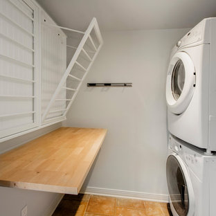 Inspiration for a mid-sized traditional u-shaped dedicated laundry room in Dallas with wood benchtops, grey walls, terra-cotta floors, a stacked washer and dryer, orange floor and brown benchtop.