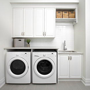 Photo of a traditional single-wall laundry room in Toronto with an undermount sink, raised-panel cabinets, white cabinets, white walls, a side-by-side washer and dryer and grey benchtop.