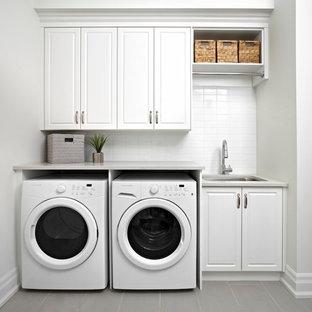 Esempio di una lavanderia classica con lavello sottopiano, ante con bugna sagomata, ante bianche, pareti bianche, lavatrice e asciugatrice affiancate e top grigio