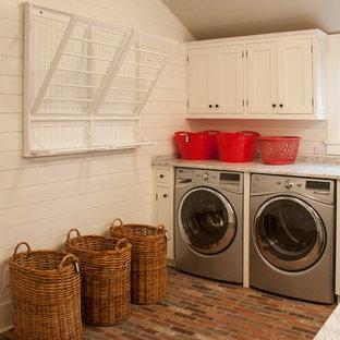 Foto på en stor maritim l-formad tvättstuga enbart för tvätt, med en undermonterad diskho, skåp i shakerstil, vita skåp, vita väggar, tegelgolv och en tvättmaskin och torktumlare bredvid varandra