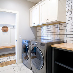 Mid-sized transitional single-wall ceramic tile and white floor dedicated laundry room photo in Other with shaker cabinets, white cabinets, wood countertops, gray walls, a side-by-side washer/dryer and brown countertops