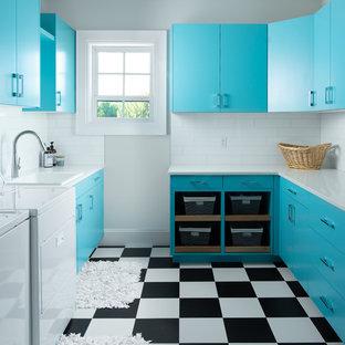 Exempel på en klassisk vita vitt tvättstuga enbart för tvätt, med en nedsänkt diskho, släta luckor, vita väggar, en tvättmaskin och torktumlare bredvid varandra, flerfärgat golv, vinylgolv och blå skåp