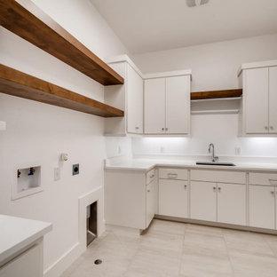 Cette image montre une buanderie minimaliste en L dédiée et de taille moyenne avec un évier posé, un placard à porte plane, des portes de placard blanches, un plan de travail en marbre, un mur blanc, un sol en carrelage de céramique, des machines côte à côte, un sol beige, un plan de travail blanc, un plafond en lambris de bois et du lambris de bois.