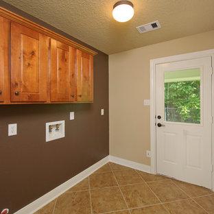 Esempio di una sala lavanderia classica di medie dimensioni con ante con bugna sagomata, ante in legno scuro, top in cemento, pareti beige, pavimento in gres porcellanato, lavatrice e asciugatrice affiancate e pavimento beige
