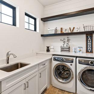 Foto på en lantlig vita l-formad tvättstuga enbart för tvätt, med en undermonterad diskho, vita skåp, bänkskiva i kvarts, vita väggar, travertin golv, en tvättmaskin och torktumlare bredvid varandra, luckor med infälld panel och beiget golv