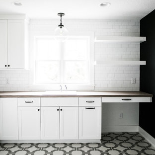 This is an example of a large country l-shaped separated utility room in Minneapolis with a built-in sink, flat-panel cabinets, white cabinets, laminate countertops, black walls, vinyl flooring and a stacked washer and dryer.