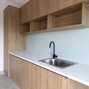Esempio di una sala lavanderia contemporanea di medie dimensioni con lavello a vasca singola, paraspruzzi blu, paraspruzzi in gres porcellanato, pavimento in gres porcellanato e pavimento grigio