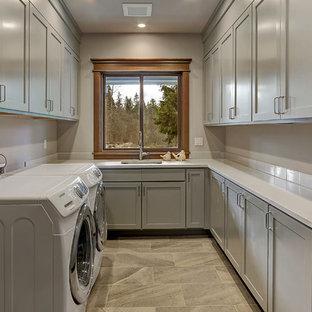 Klassisk inredning av en stor vita u-formad vitt tvättstuga, med en enkel diskho, skåp i shakerstil, grå skåp, beige väggar, klinkergolv i porslin och en tvättmaskin och torktumlare bredvid varandra