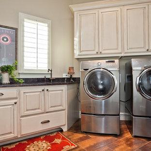 Idéer för en klassisk tvättstuga enbart för tvätt, med luckor med upphöjd panel, beige skåp, beige väggar, en tvättmaskin och torktumlare bredvid varandra och orange golv