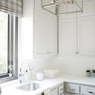 Cette image montre une buanderie craftsman dédiée et de taille moyenne avec un évier encastré, un placard avec porte à panneau surélevé, des portes de placard grises, un plan de travail en quartz et un mur blanc.