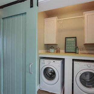 Idéer för en mellanstor klassisk gula linjär liten tvättstuga, med vita skåp, en tvättmaskin och torktumlare bredvid varandra och luckor med infälld panel