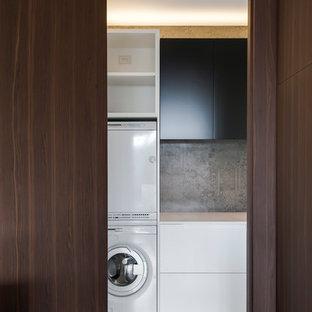 Ispirazione per una lavanderia moderna di medie dimensioni con ante in legno bruno, top in superficie solida, paraspruzzi grigio, paraspruzzi con piastrelle di cemento e pavimento con piastrelle in ceramica