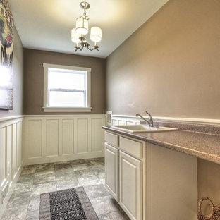 Foto di una sala lavanderia american style di medie dimensioni con lavello da incasso, ante bianche, top in laminato, pareti beige, pavimento in linoleum, lavatrice e asciugatrice affiancate e ante con bugna sagomata