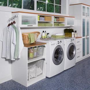 Foto på ett mellanstort funkis brun linjärt grovkök, med linoleumgolv, skåp i shakerstil, vita skåp, träbänkskiva, vita väggar och en tvättmaskin och torktumlare bredvid varandra
