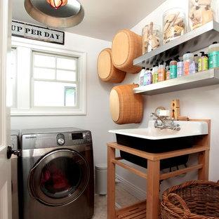 Modelo de cuarto de lavado ecléctico con fregadero encastrado y lavadora y secadora juntas