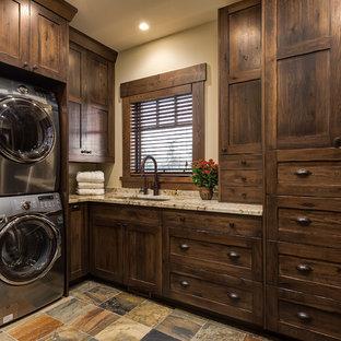 Immagine di una grande sala lavanderia stile rurale con lavello sottopiano, ante in stile shaker, ante in legno bruno, top in granito, pavimento in ardesia, lavatrice e asciugatrice a colonna, pareti beige e top beige
