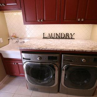 Immagine di una lavanderia country con ante con bugna sagomata, ante in legno bruno e lavatrice e asciugatrice affiancate