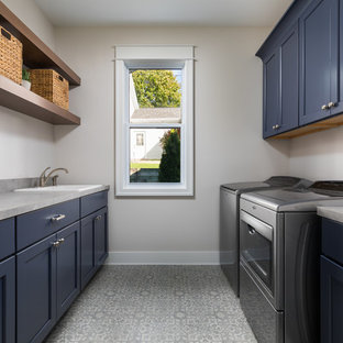 Example of a large coastal galley vinyl floor and gray floor dedicated laundry room design in Grand Rapids with a drop-in sink, blue cabinets, laminate countertops, a side-by-side washer/dryer, gray countertops, shaker cabinets and beige walls