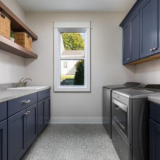 Idee per una grande sala lavanderia stile marino con lavello da incasso, ante blu, top in laminato, pavimento in vinile, lavatrice e asciugatrice affiancate, pavimento grigio, top grigio, ante in stile shaker e pareti beige